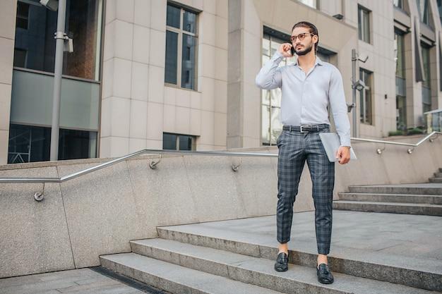 Серьезный и созвучный стильный бизнесмен стоит и позирует. он держит ноутбук в руке и телефон близко к уху. он смотрит прямо вперед.