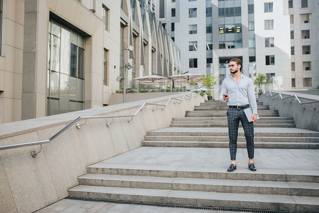 Серьезный и красивый молодой человек стоять и ставить. он смотрит направо. бизнесмен держит телефон и ноутбук в руках. он окружен зданиями.