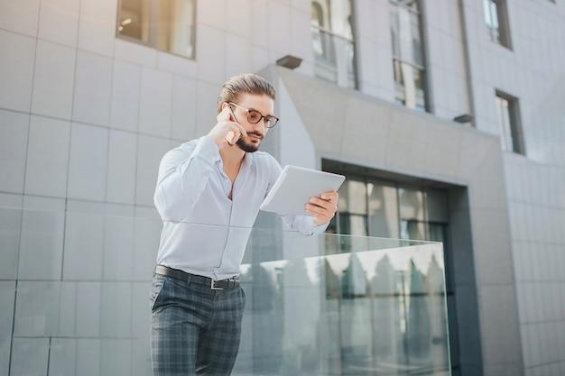 Занят и красивый мужчина стоит и держит планшет. он смотрит на экран и одновременно говорит по телефону. этот парень многозадачный человек.