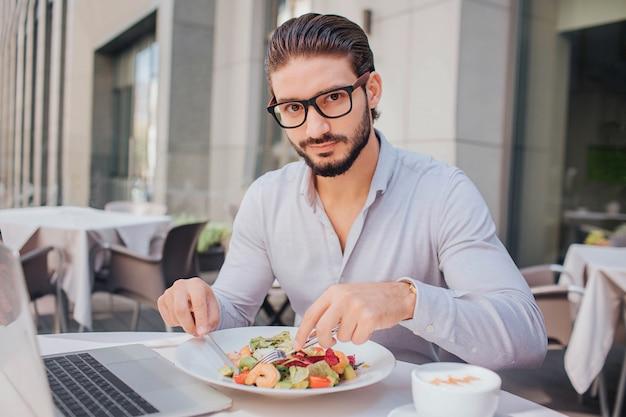 Молодой красавец сидит за столом и обедает. он смотрит на камеру. парень позирует. он готов съесть салат. за столом ноутбук и чашка кофе.