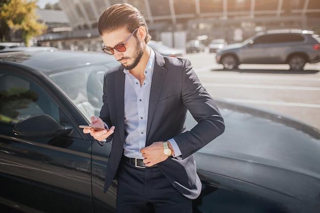 ハンサムで忙しい若い男は黒い車に立っています。彼は電話を持って見ています。外は晴れです。