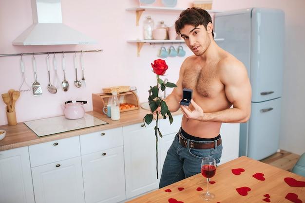 ハンサムで情熱的な若い男は、テーブルでキッチンに立っています。彼は赤いバラとリング付きの箱を持っています。若い男が立ちポーズ。