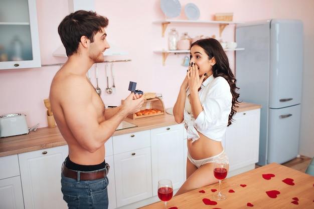 Горячие пары стоят на кухне. молодой человек держать коробку с кольцом. он делает предложение женщине. она выглядит счастливой и взволнованной. они полуголые.
