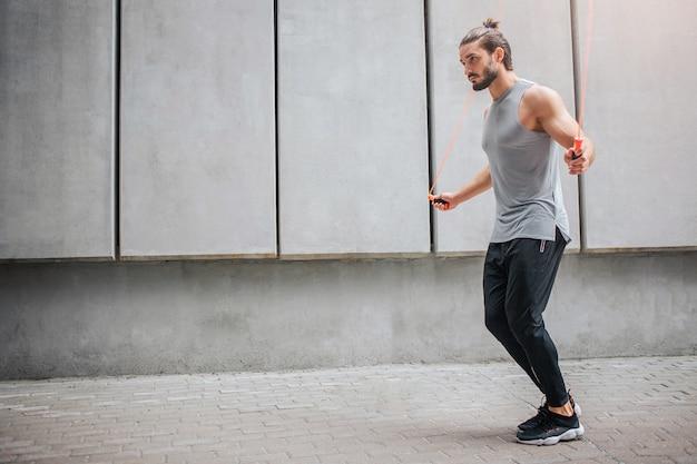 外で運動する強力な若い男。彼は灰色の壁でそれをします。男はジャンプしてオレンジ色のロープを使用します。彼は集中しています。若い男は一人です。