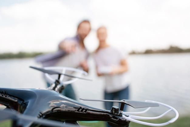 すべての注意は、空を飛んでいるドローンに集中しています。カップルによって制御されます。彼らは水の端に立っています。男はドローンを指しています。