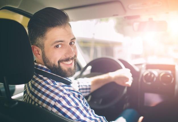 Красивый элегантный серьезный мужчина водит машину