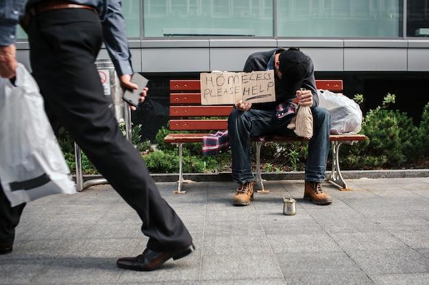 Бедный и пьяный мужчина сидит на скамейке и держит в руках картон с надписью «бездомный, пожалуйста, помогите». он положил голову на руку, в которой у него есть бутылка напитка. парень спит