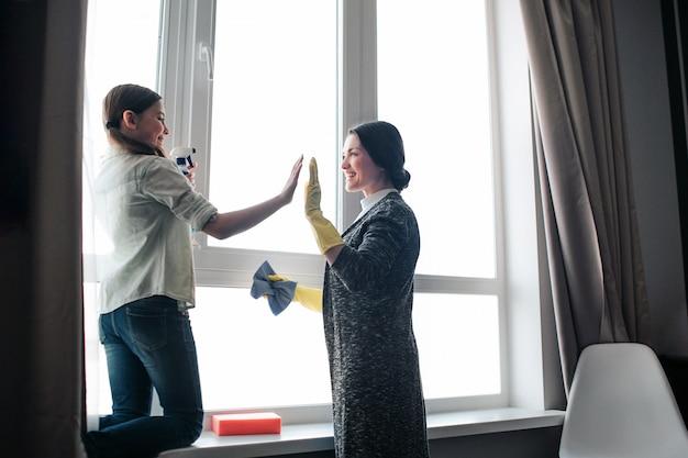 美しいブルネットの白人の母と娘が部屋で一緒に窓を掃除します。チームワーク。彼らはお互いにハイファイブを与えます。結果に満足しています。明け。