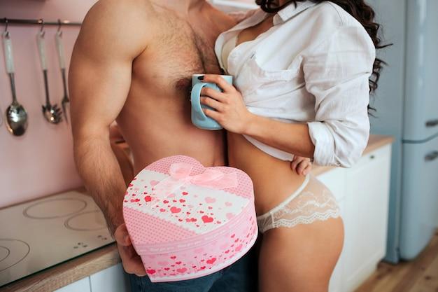 キッチンでしっかりと構築された若い男女のビューをカットします。彼はピンクの箱を手で持っています。女性は青いカップを持っています。