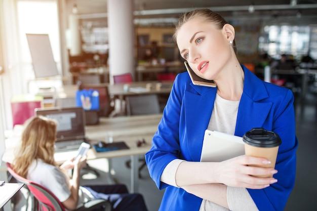 真面目で思慮深い人が電話で話しています。彼女は一杯のコーヒーとノートを持っています。女の子は窓を探しています。