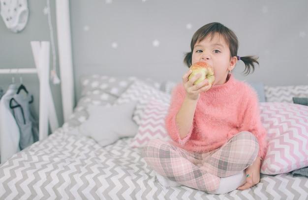 小さな女の子はリンゴを食べる