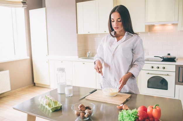 深刻な集中若い女性は、キッチンと料理に立っています。