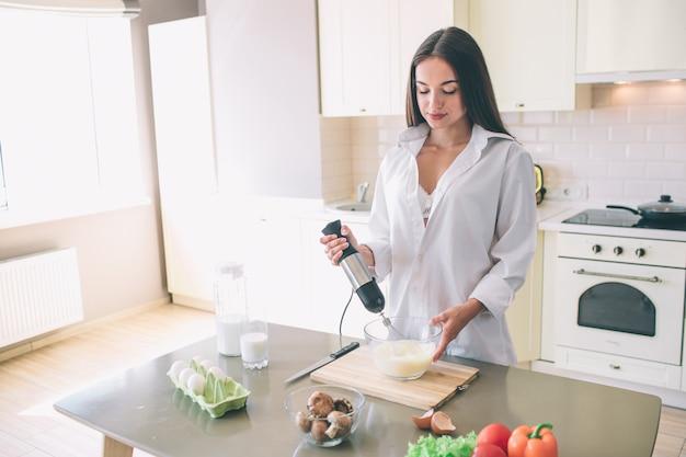 美しい少女の親密な写真は、キッチンと料理に立っています。