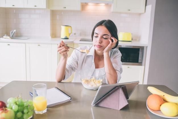疲れて退屈少女はテーブルに座って、ミルクとコーンフレークでスプーンを見ています。