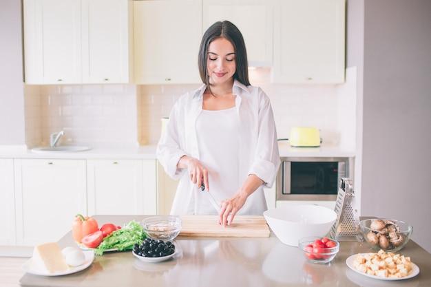 若い女性が台所で料理。彼女は立って野菜を切ります。