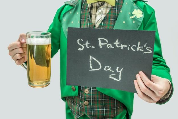 聖パトリックの日と書かれた言葉でビールと暗いタブレットのマグカップを保持している緑のスーツを着た男のビューをカットします。