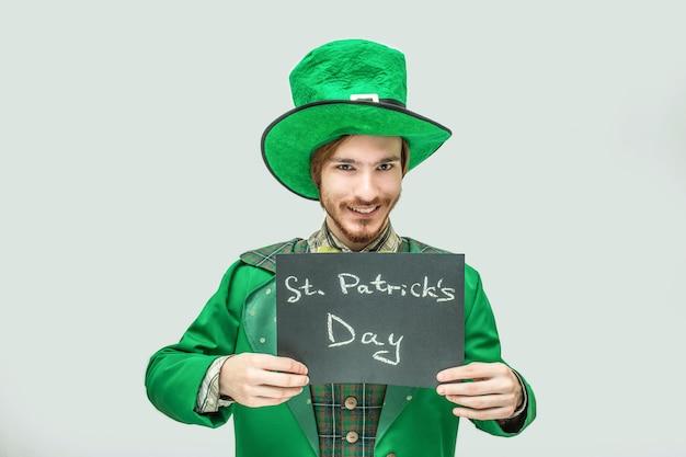 聖パトリックの日の書かれた言葉で暗いタブレットを保持している緑のスーツで幸せな若い男。