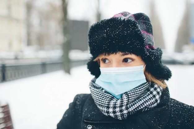 Молодая женщина носить маску для защиты от коронавируса болезни. стоять на улице зимой. опасно для инфекционных и бактериальных заболеваний. готовьтесь к респираторным заболеваниям.