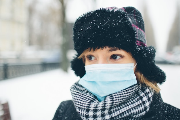Молодая женщина носить маску для защиты от коронавируса болезни. портрет серьезного спокойного и мирного женского человека стоит снаружи в зимнее время. болезнь или бактериальная инфекция.