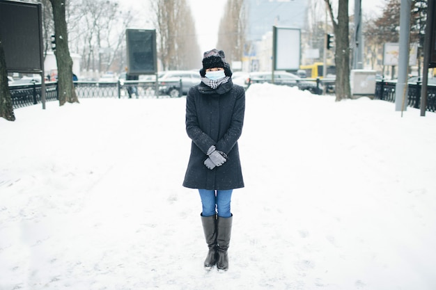 Молодая женщина носить маску для защиты от коронавируса болезни. изображение молодого тонкого женского лица стоять в середине на медленной земле зимой. будьте готовы к опасной инфекции или болезни.