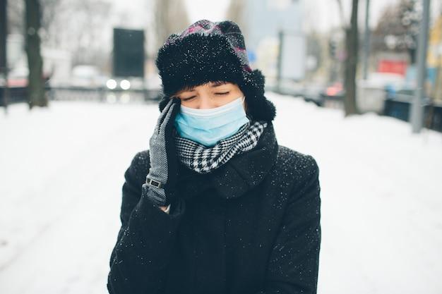 Молодая женщина носить маску для защиты от коронавируса болезни. головная боль и сильная боль. женщина страдает от этого. первая реакция на инфекцию или болезнь. бактерии хаззарда.