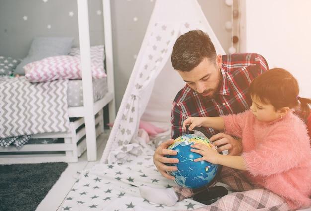 かわいい小さな娘と彼女のハンサムな若いお父さんは子供部屋で一緒に遊んでいます。お父さんと子供の幸せな家族は旅行を準備し、ルートマップを学ぶ