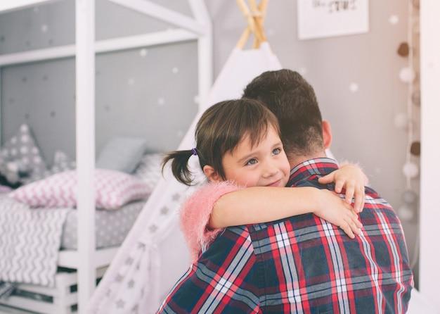 かわいい小さな娘と彼女のハンサムな若いお父さんは、子供部屋で一緒に遊んでいます。パパと子供は、寝室の床に座って一緒に時間を過ごします。