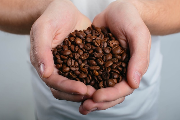 コーヒーを保持している男性とクローズアップの香りを楽しんでいます