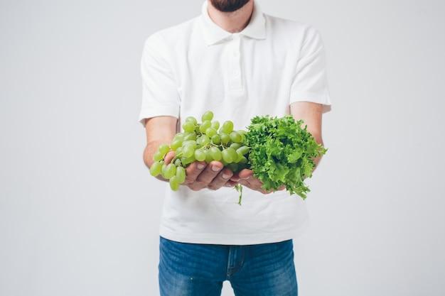 Человек, держащий салаты и виноград, крупным планом. концепция. изолированные на белом