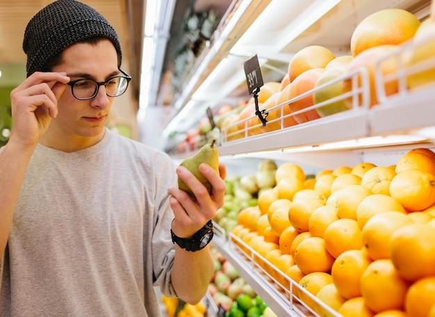 Это должно быть хорошо. красивые молодые человеки держа грушу и хозяйственную сумку пока стоящ в продовольственном магазине
