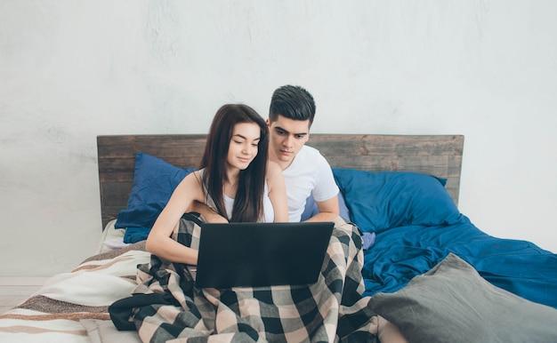 若い男性と女性はコンピューターで作業しているか、ベッドの上のインターネットで情報を探しています。
