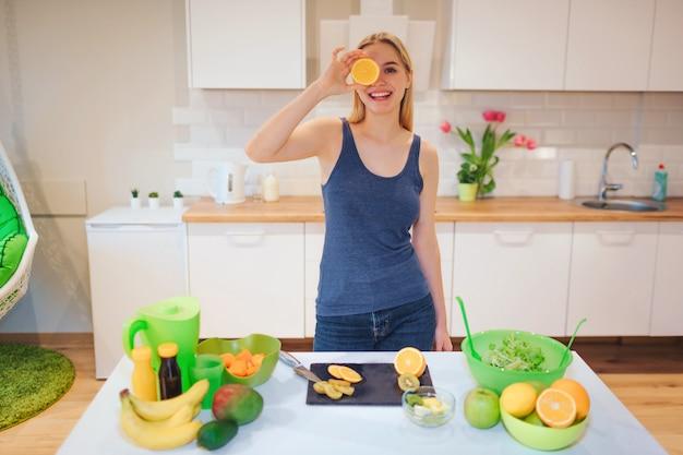 Молодая блондинка улыбается держит кусок апельсина
