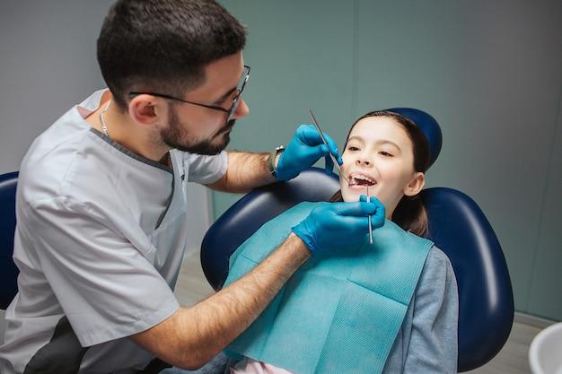 若い男性歯科医は女の子の歯をチェックします。