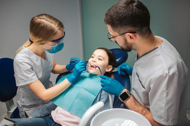 女性歯科医が女の子の歯をチェック