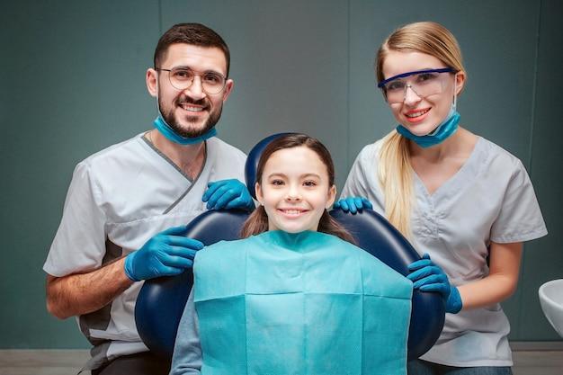 女の子と陽気な男性と女性の歯科医。