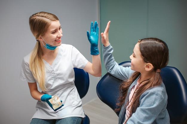 歯科用椅子の女の子にハイファイブを与える男性歯科医