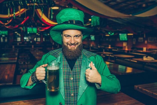 Счастливый и позитивный молодой человек в зеленом костюме в пабе. он держит кружку пива и показывает большой палец вверх. молодой человек доволен.