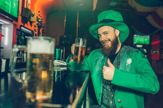 Счастливый и возбужденный бородатый молодой человек в костюме святого патрика сидит за барной стойкой в пабе и держит кружку пива. он поднял большой палец вверх. еще одна кружка пива стоит рядом с камерой.