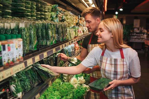 食料品店の緑の棚に立っている若い男性と女性
