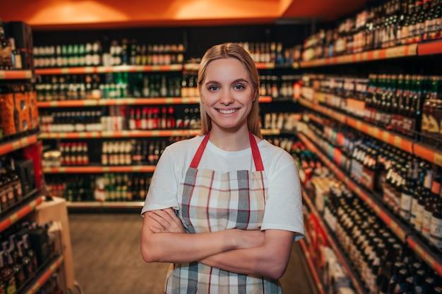 アルコール棚の中で食料品店に立っている若い女性
