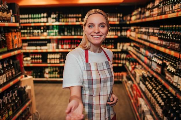 食料品店のアルコール棚に立っている若い女性