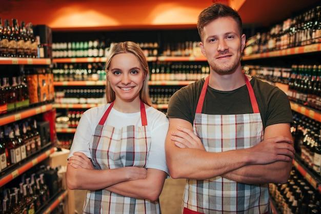 プロの若い男性と女性が食料品店に立ってポーズ