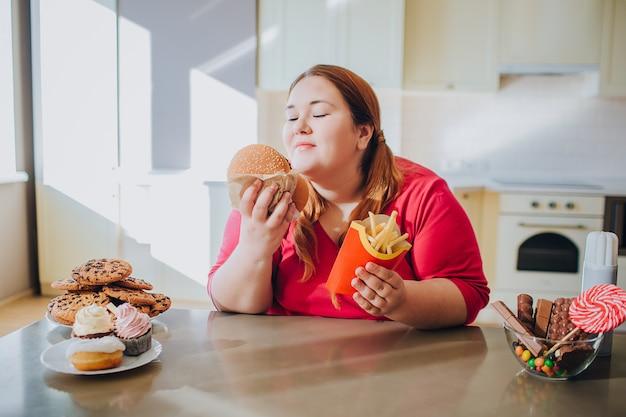 座っているとジャンクフードを食べるキッチンで脂肪の若い女性。