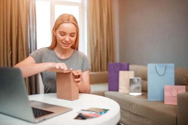 若い笑顔の買い物客はテーブルに座っている間彼女の小包の開梱