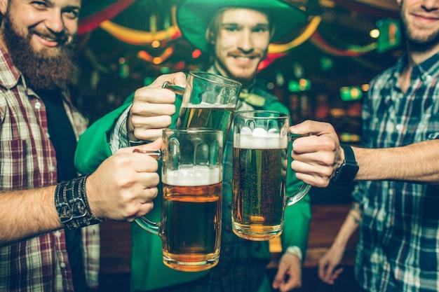 陽気な幸せな友人がパブで一緒に立って、応援します。彼らはお互いの近くにビールのジョッキを保持します。人々は笑います。彼らはお祝いの近くの緑のスーツを着ています。