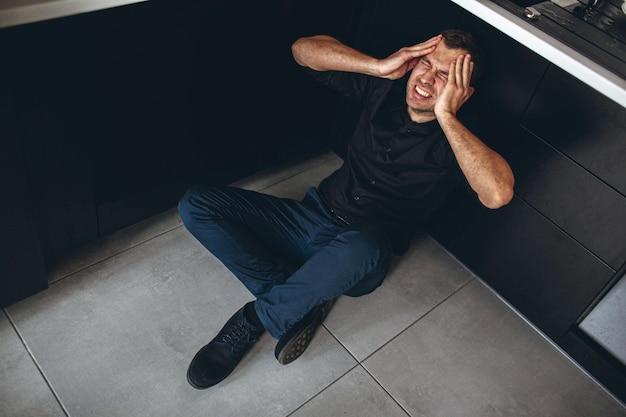 青年実業家は床とキッチンの上に座るし、頭の上の手を保持します。頭痛とひどい痛み。男は無秩序または生理学的問題に苦しんでいます。キッチンで一人で。人から切り離してください。
