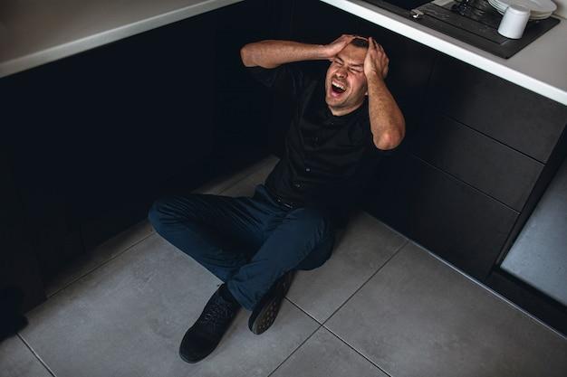 キッチンと悲鳴の床に座って狂牛病の絶望的な男のカラフルな写真。頭に手をかざします。心理的な問題と障害。うつ病と狂気。