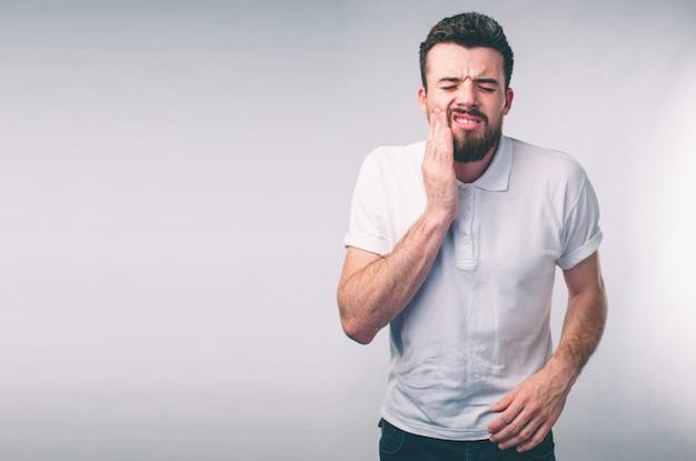歯の問題。歯の痛みを感じる男。強い歯の痛みに苦しんでいるひげを生やした少年のクローズアップ。魅力的な男性は痛みを伴う歯痛を感じています。歯科健康とケアのコンセプト