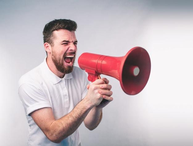 Портрет человека крича используя мегафон над стеной.