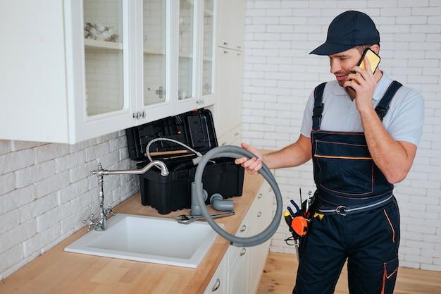 Молодой водопроводчик говоря на телефоне в кухне на раковине. он держит шланг. услуги ремонта. ящик для инструментов на столе. дневной свет.